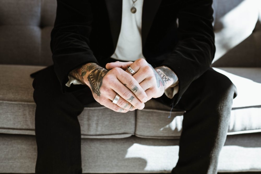 Tattooed man sitting on couch holding hands
