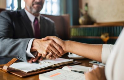 Two people shaking hands over a desk in a formal setting