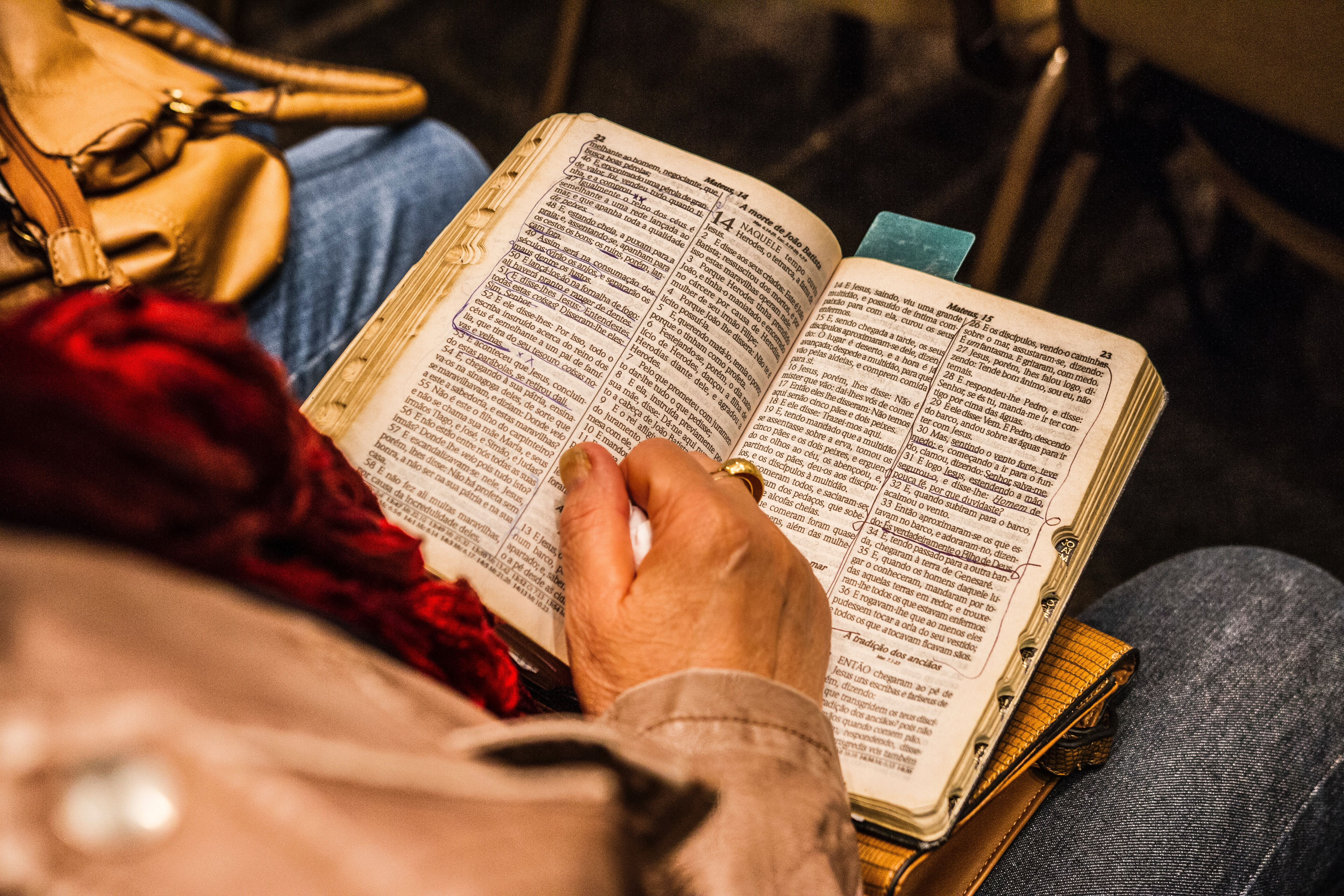 Elderly person reading old marked-up religious book